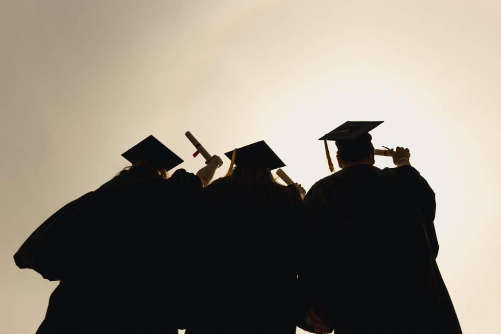 silhouette of three grad-students